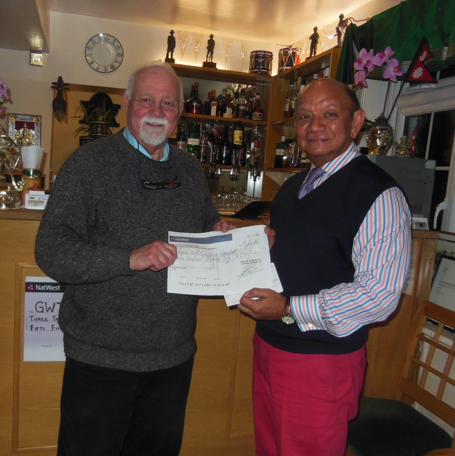 Mani presenting a cheque for £200 to the Royal British Legion Grayshott. The money was raised during the Remembrance Sunday Curry Lunch